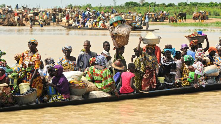 People taking a boat across a river in Djenne, Mali