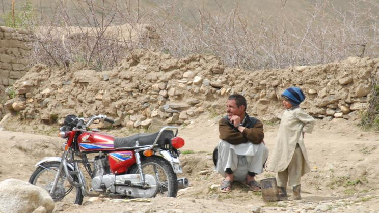 Man and boy sit next to a motorbike in Nechem, Afghanistan