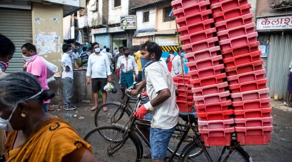 Milk vendor pushes bicycle through crowded market area in Dharavi slum during nationwide lockdown as a preventive measure against the spread of the COVID-19 coronavirus
